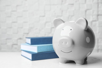 Piggy bank with stack of books on table