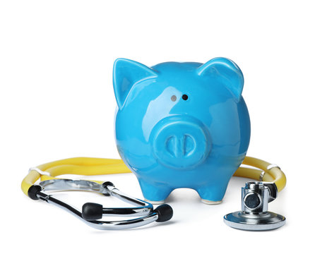 Piggy bank with stethoscope isolated on white