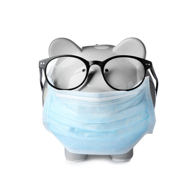 Piggy bank with glasses and face mask isolated on white