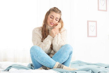 Beautiful smiling young woman in cozy warm sweater sitting on bed at home