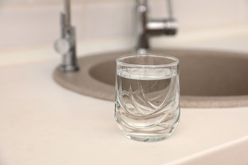 Glass of water on counter near sink. Space for text