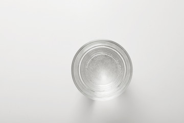 Glass of fresh water on white background, top view
