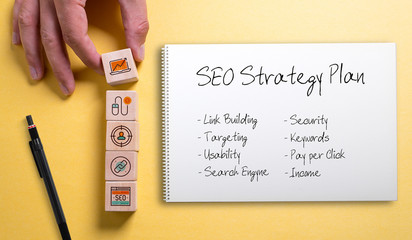Cubes and notebook with SEO strategy on bright colorful paper background