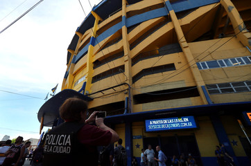 A police woman takes a photo of Boca Juniors' La Bombonera stadium in Buenos Aires