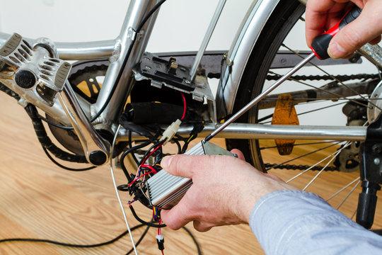 Mechanic repairing electric bicycle in his workshop