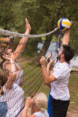 group of young friends playing Beach volleyball