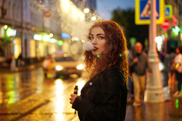 Young attractive red-haired girl smokes electronic cigarette. She is in leather jacket standing on road in street of night city. Wet asphalt after rain.