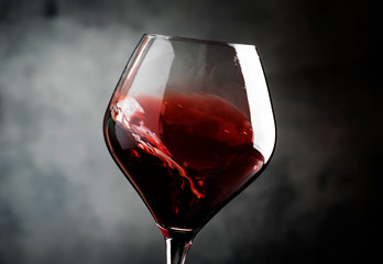 Spanish dry red wine, splash in glass, from the tempranillo grape, gray stone background, defocused in motion image, shallow depth of field