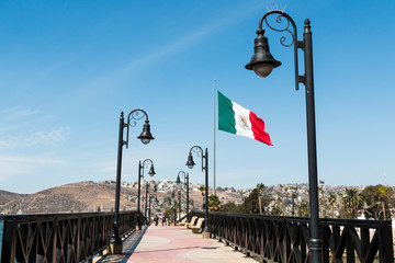 Pedestrian bridge leading to the marina and waterfront shops in Ensenada, Mexico, with a giant flag of Mexico.
