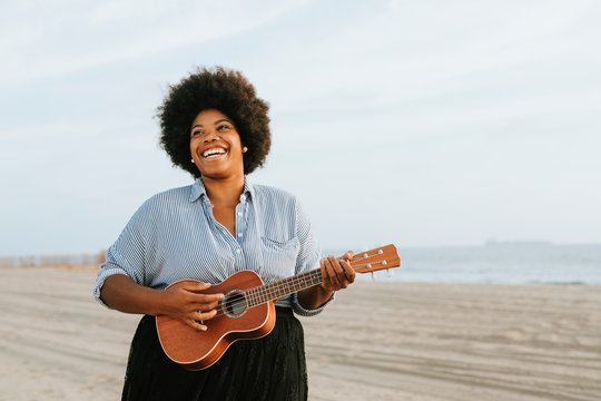 African American musician playing ukulele at the beach