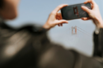 Woman using her phone to take a picture of the Golden Gate Bridge, San Francisco