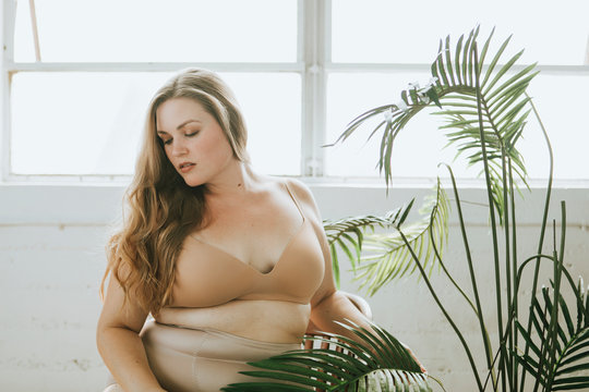 Beautiful and confident plus size woman in nude underwear