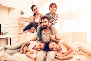 Portrait of Cute Smiling Family Sitting on Sofa