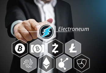 Business man points his finger at Electroneum coin icon among others Cryptocurrency on Virtual Touch Screen , Conceptual