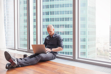 Young attractive stylish bald man in a business suit sitting on the floor with a laptop in his office in a skyscraper, business, finance, success
