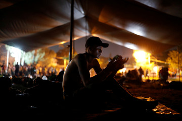 A migrant, part of a caravan traveling en route to the United States, uses his cellphone while he rests with fellows migrants in a sport complex that is currently used as a temporary shelter, in Matias Romero Avendano, Mexico November 8, 2018. REUTER