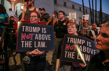 People gather in front of City Hall to take part in a protest to protect the investigation led by Special Counsel Robert Mueller, in Los Angeles