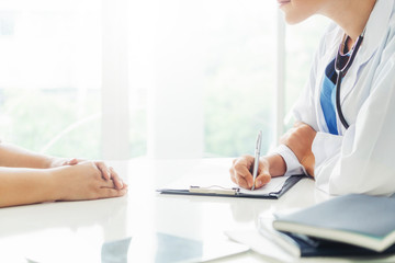 Woman doctor talks to female patient while writing on the patient health record in hospital office. Healthcare and medical service.