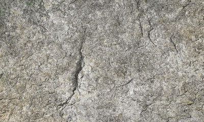 Gray and brown textured stone granite background. Flat dry stone granite rock texture with fissures and shadows.