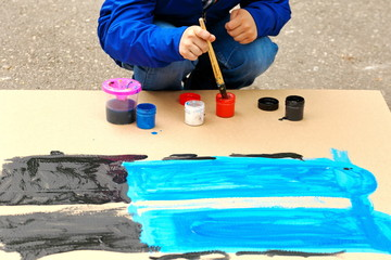 The hand of the child paints a blob with a brush.
