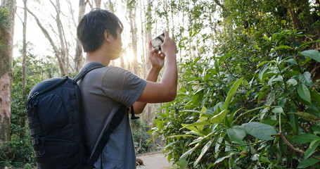 Man go hiking and taking photo on cellphone