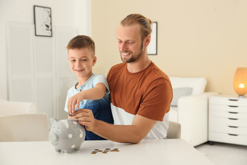 Father and son putting coin into piggy bank at home