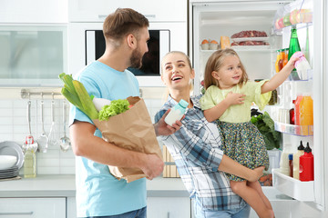 Happy family putting products into refrigerator in kitchen