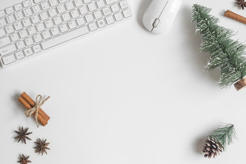 Flat lay Office desk table with computer wireless keyboard, mouse, mini Christmas tree, spices, pine cone decoration on white table. Top view with copy space