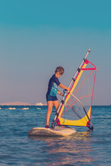 One child, a caucasian boy of 8-10 years old learning to windsurf sailing through the calm sea waters at sunset on vacation