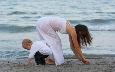 Child and mother looking for sea shells in the sand on the beach