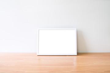 Mock up horizon photo frame on woodden table.