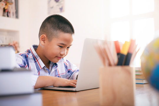 Boy using his laptop to learning online.