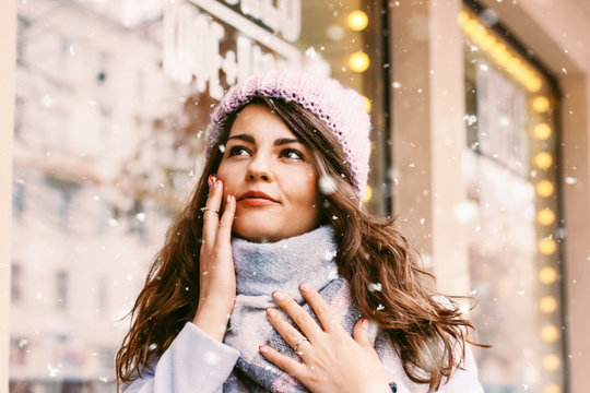 Portrait of young beautiful woman in coat and hat enjoing the fi
