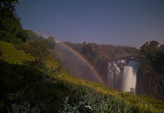 Victoria Falls,Zimbabwe-August 17, 2016: A lunar rainbow or a moonbow on the Victoria Falls observed within 2 days of full moon. Since the lunar rainbows are much fainter than the day-time ones, long-