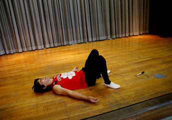 Japanese rope skipper Hijiki Ikuyama lies on the floor after his attempt at a new Guinness record in the most double under crossovers while skipping backwards in 30 seconds, on the annual Guinness World Records Day at an elementary school in Tachikawa