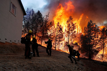 U.S. Forest Service firefighters monitor a back fire while battling to save homes at the Camp Fire in Paradise