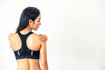 Sporty woman touching shoulder in fitness gym. Healthy lifestyle concept.