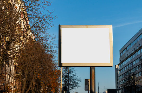 The big white billboard in the city during day time. Billboard mock-up on the blue sky and city background.