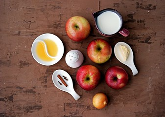 Ingredients for the preparation of apple soup puree: fresh apples, butter, onions, cream, honey, spices. Top view.