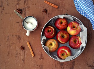 Fresh organic apples prepared for baking, with sugar and spices in a round baking dish on a brown background. Healthy dessert concept.