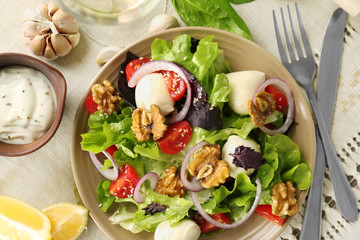 Delicious fresh salad with walnuts on plate