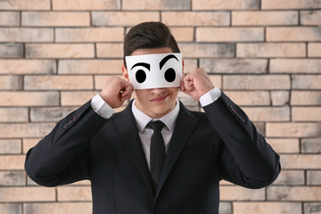Emotional young businessman hiding face behind sheet of paper with drawn eyes against brick wall