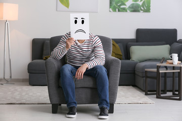Young man hiding face behind sheet of paper with drawn emoticon while sitting in armchair at home
