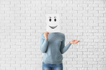 Young woman hiding face behind sheet of paper with drawn emoticon against white brick wall