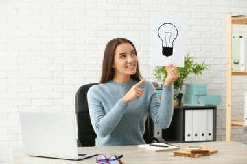 Emotional young woman holding paper sheet with drawn light bulb as symbol of idea while sitting at table