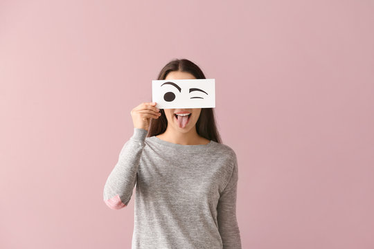 Emotional young woman hiding face behind sheet of paper with drawn eyes on color background