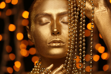 Wall Mural - Beautiful young woman with golden paint on her body and beads against defocused lights, closeup