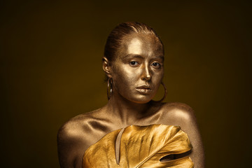 Beautiful young woman with golden paint on her body and tropical leaf against dark background