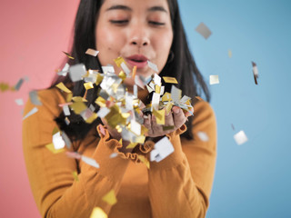 Happy Asian woman blowing with falling silver and golden paper glitter down.
