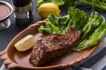 Grilled sturgeon on a plate with lemon and sauce. Grilled sturgeon on a plate